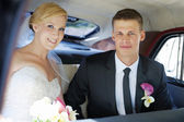 Bride and groom sitting in a car — Stock Photo