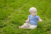 Baby sitting on a green grass — Stock Photo