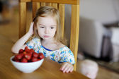 Thoughtful girl with fresh strawberries in a bowl — Foto de Stock