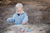 Adorable toddler girl playing with sidewalk chalk — Stock fotografie