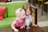 Two sisters drinking milkshake — Stock Photo