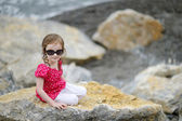Adorable little girl sitting on a rock — Stock Photo