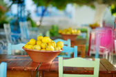 A dish of lemons in typical greek outdoor cafe — Stockfoto