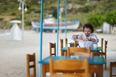Young man drinking coffee in outdoor restaurant — Stock Photo