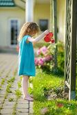 Cute little girl watering flowers — Stock Photo