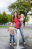 Happy family having fun by a fountain — Stock Photo