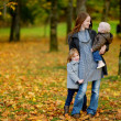 Young mother and her two little daughters at fall — Stock Photo #43460709