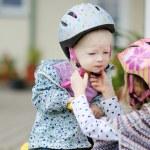 Little girl hepling her sister to put a helmet — Stock Photo #43460757