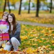 Young mother and her little daughter at fall — Stock Photo #43460969