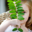 Adorable little girl hiding behind a leaf — Stock Photo #43461361