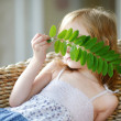 Adorable little girl hiding behind a leaf — Stock Photo #43461619