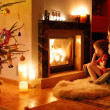 Young mother and her daughters by a fireplace — Stock Photo #43461797