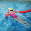 Little girl learning to swim with pool noodle — Stock Photo #43461829