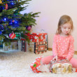 A girl unwrapping presents on Christmas morning — Stock Photo