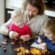 Father and his kids making chestnuts creatures — Stock Photo #43463365