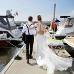 Happy bride and groom walking on pier — Stock Photo #43465273