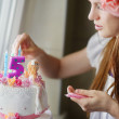 Young mother decorating daughters birhtday cake — Stock Photo #43466159