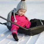 Winter fun: a girl having a ride on a snow shovel — Stock Photo