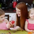 Mother and her daughters painting Easter eggs — Stock Photo #43467029