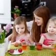 Mother and her daughters painting Easter eggs — Stock Photo #43467057
