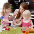 Mother and her daughters painting Easter eggs — Stock Photo #43467197