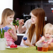 Mother and her daughters painting Easter eggs — Stock Photo