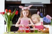 Two little sisters painting Easter eggs — Stock Photo