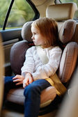 Adorable little girl sitting in car seat — Stock Photo