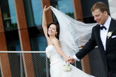 Happy bride and groom in a city — Stock Photo