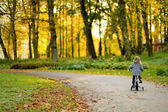 Adorable girl riding a bike on autumn day — 图库照片