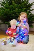 Two sisters decorating Christmas tree — Stock Photo