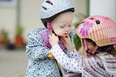 Маленькая девочка hepling сестре положить шлем — Стоковое фото