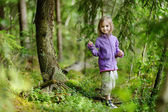Adorable little girl hiking in the forest — Stock Photo