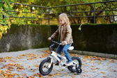 Adorable girl riding a bike on autumn day — Stok fotoğraf