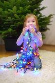 Malá dívka zdobení vánoční strom — Stock fotografie