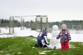 Little girls painting a snowman — Foto Stock