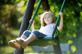 Adorable girl having fun on a swing — Stock Photo