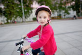 Adorable girl riding a bike — Stok fotoğraf