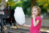 очаровательны маленькая девочка ест зубочистки конфеты на открытом воздухе — Стоковое фото