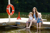 Mother and her children sitting on a wooden pier — Stock Photo