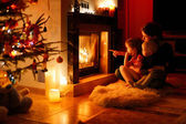 Young mother and her daughters by a fireplace — Stock Photo