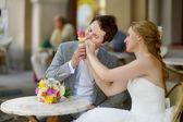 Bruid en bruidegom met een ijsje buitenshuis — Stockfoto
