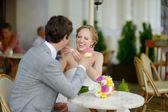 Bride and groom having an ice cream outdoors — Stockfoto