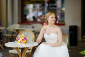 Young bride having an ice cream in outdoor cafe — Stock Photo