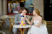 Bride and groom having an ice cream outdoors — Stock Photo