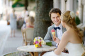 Bride and groom having an ice cream outdoors — Stock fotografie