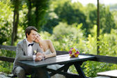 Bride and groom sitting at an outdoor cafe — Photo