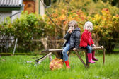 Two sisters sitting on a wooden bench on autumn — Stock Photo