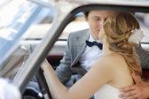 Bride and groom in a wedding car — Stock Photo