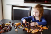 Little girl making chestnuts creatures — Stock Photo